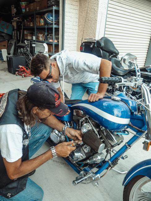 due ragazzi che controllano e sistemano moto blu