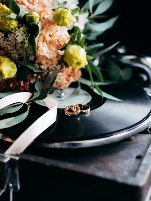 vinile con appoggiati fiori ed anelli nuziali