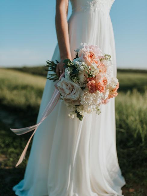 ragazza che indossa un vestito da sposa bianco e tiene bouquet di fiori