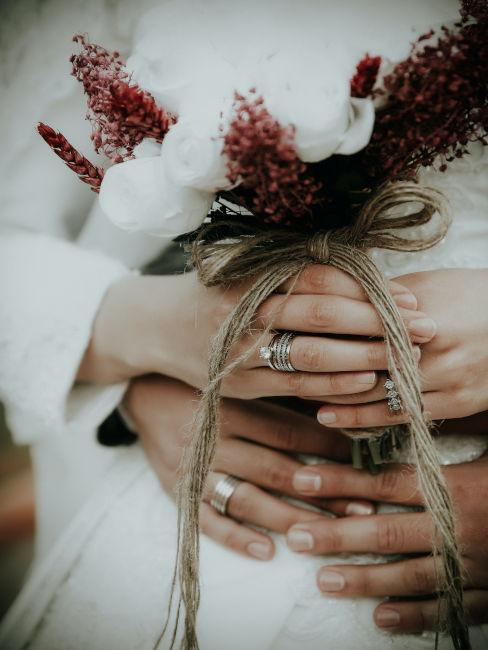 mani incrociate di due sposi con mazzo di fiori