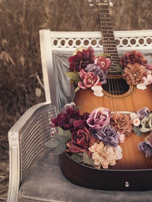 chitarra decorata con fiori appoggiata su una sedia