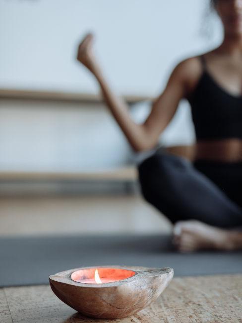 focus su candela e dietro ragazza che medita