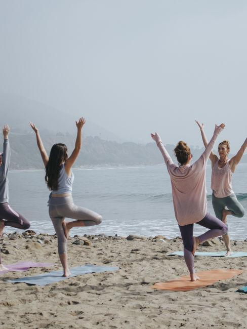 gruppo di donne che fa yoga in spiaggia