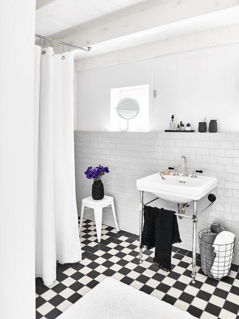 bagno bianco e nero con pavimentazione a scacchi