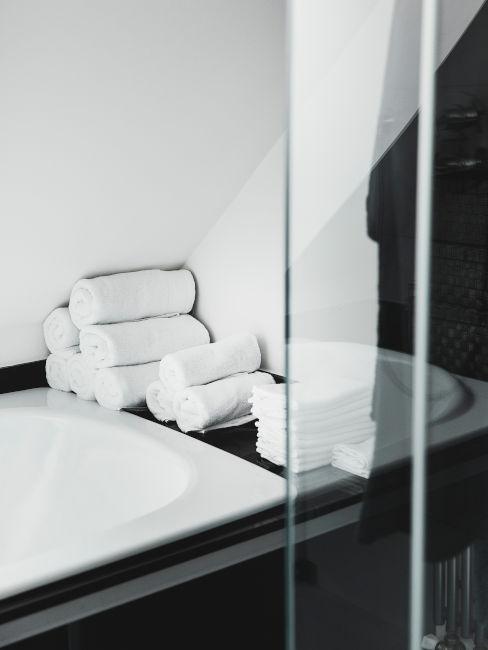 vasca da bagno con esterni neri e asciugamani bianchi