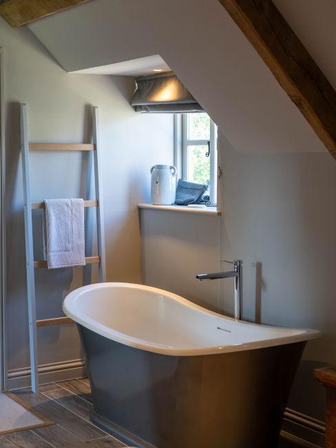 bagno con paretibianche e vasca nera all'esterno