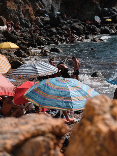 ombrelloni in spiaggia rocciosa