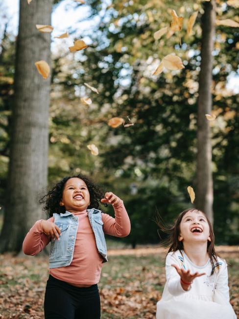 bambine in un bosco che lanciano le foglie