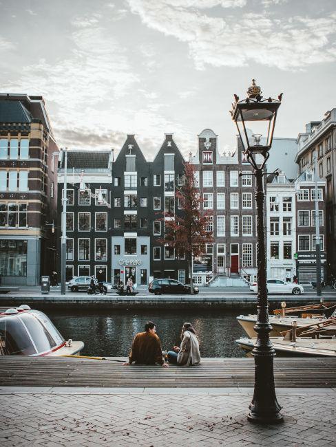 due ragazzi seduti sul canale di Amsterdam