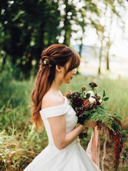 sposa che tiene in mano bouquet fiori autunnali