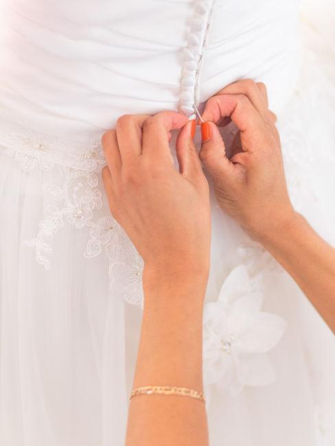 mani che allacciano vestito da sposa