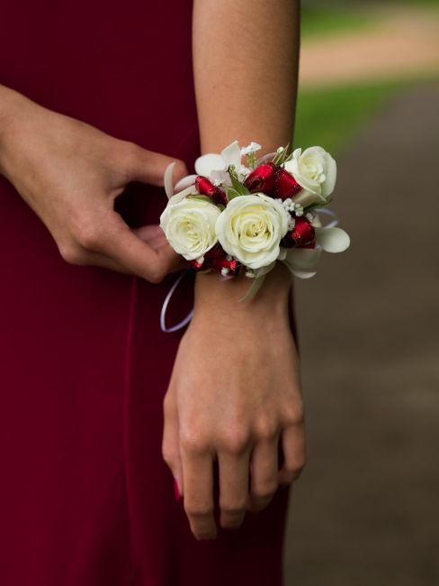 abito da damigella rosso con dettaglio bracciale fiori
