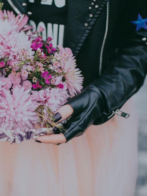 ragazza con giacca di pelle nera e bouquet viola