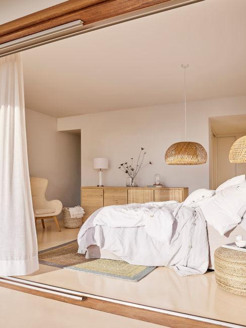 camera da letto con lenzuola bianche e mobili in legno e rattan