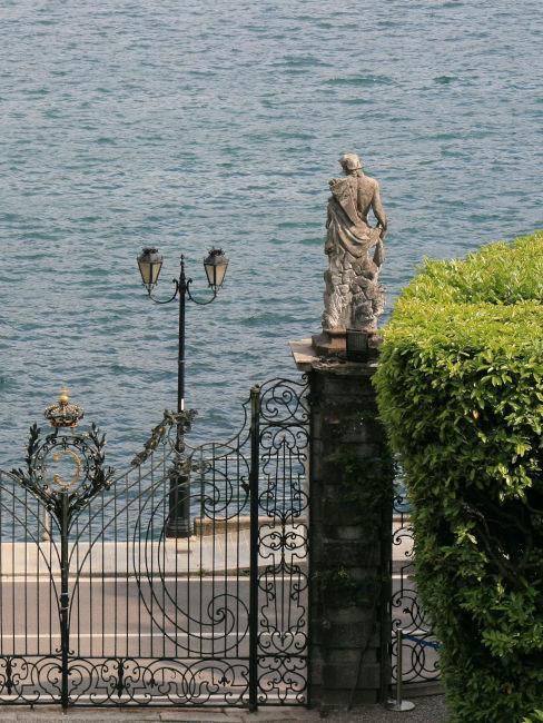 cancello in ferro batturo con statue sul lago