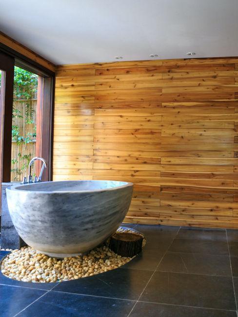 vasca in pietra in bagno con pareti in legno