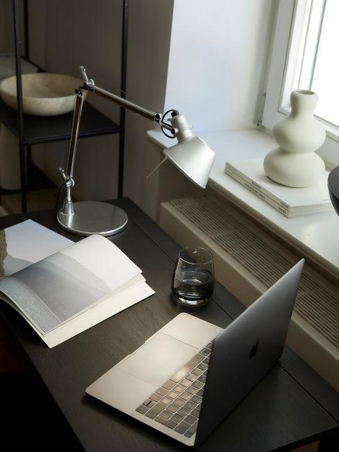 dettaglio scrivania con libro, computer e lampada