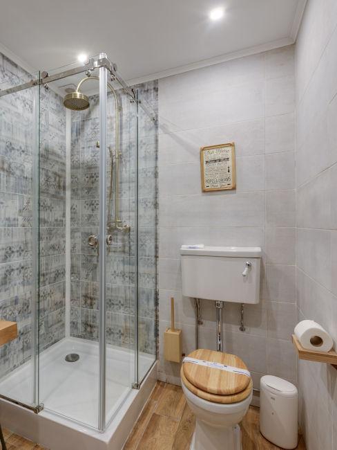 bagno con dettagli in legno e doccia piastrellata