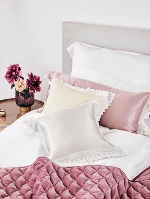 coperte e cuscini rosa su lenzuolo bianco