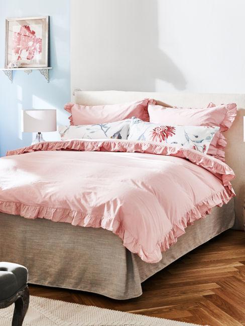 parete azzurra e letto con tessili rosa