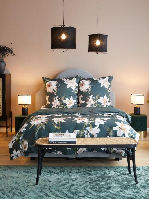 letto con tessili verde petrolio e fiori bianchi