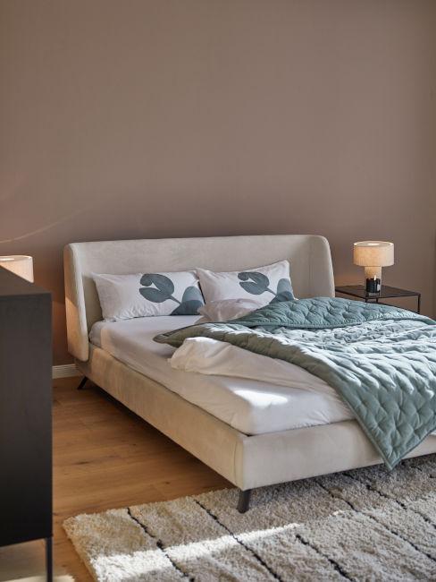 parete color tortora e letto chiaro