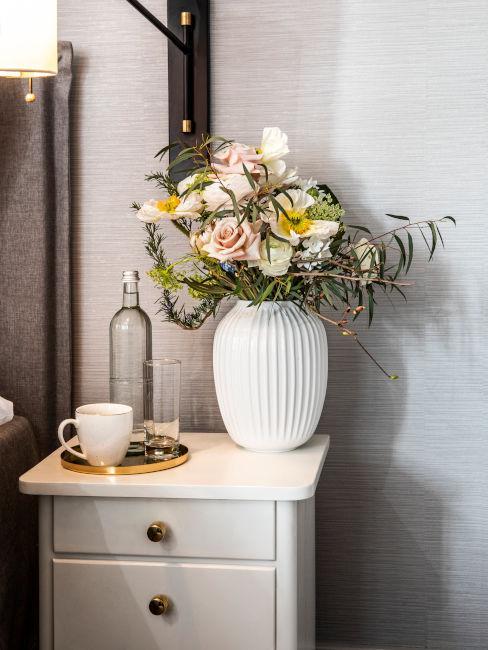 comodino in legno bianco con vaso e fiori