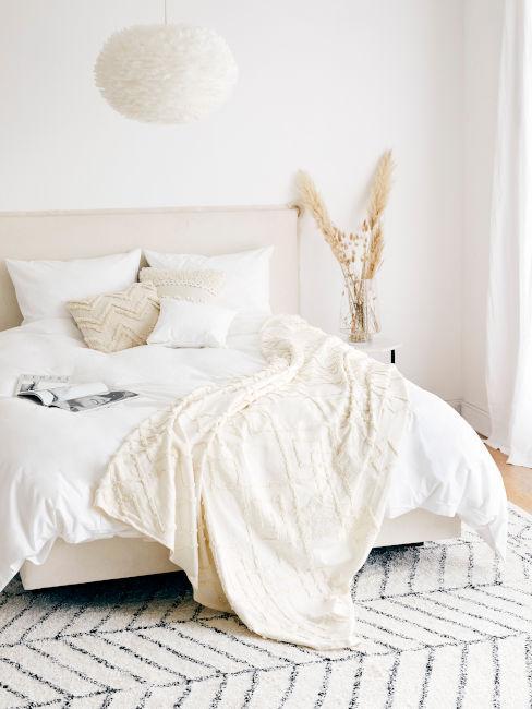 stanza con tessili chiari e pareti bianche