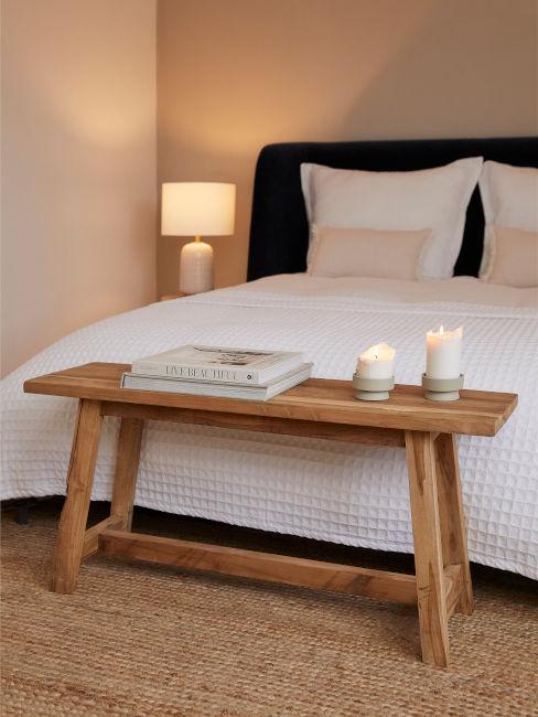 panca di legno posizionata in fondo a letto matrimoniale