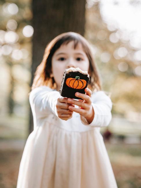 bambina che tiene in mano un gelato decorato per halloween