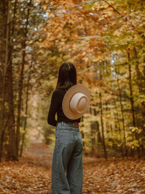 ragazza che fa passeggiata nel bosco in autunno