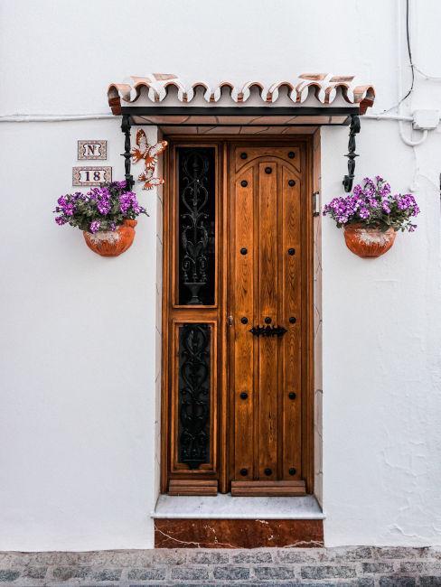 ingresso casa con porta in legno e fiori viola