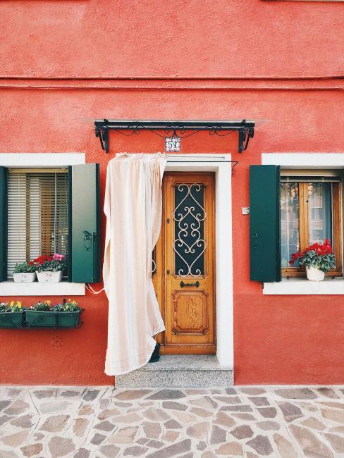 ingresso casa con porta in legno e pareti rosse