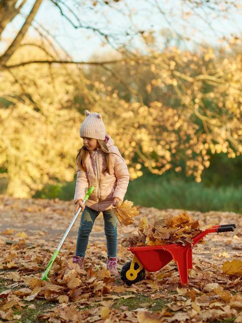 bambina che rastrella foglie in giardino