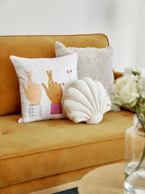divano giallo ocra con cuscini decorativi