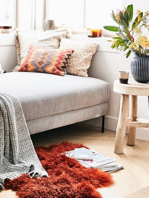 Dettaglio divano grigio con cuscini e tappeto in ecopelle color ruggine