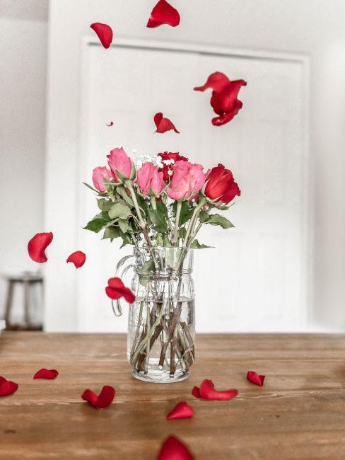 Vaso di rose con petali sul tavolo
