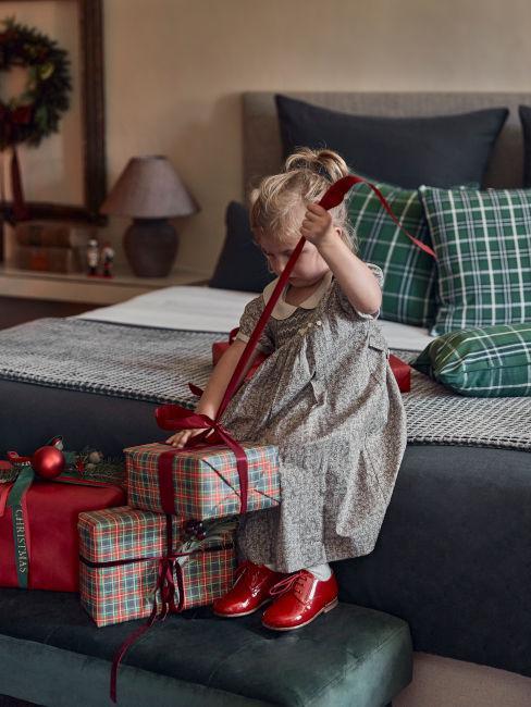 Bambina che scarta i regali di Natale