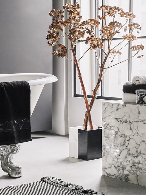 wit ligbad met marmere tafel en plant in zwarte pot