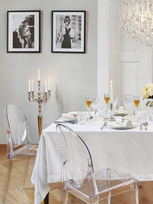 Plexigals stoelen aan gedekte tafel met kroonluchter en foto's aan de muur