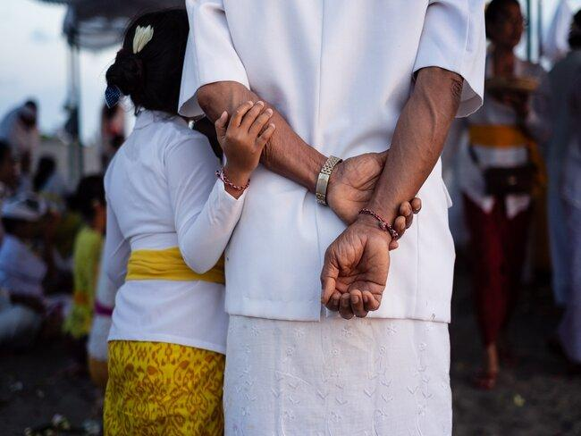 Volwassen met kind in wit en sarong van batik