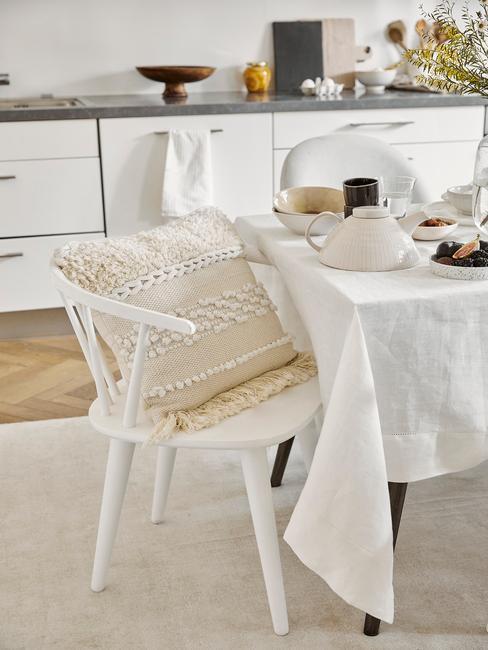 Keuken in wit met witte stoelen en tafel met tafelkleed in wit