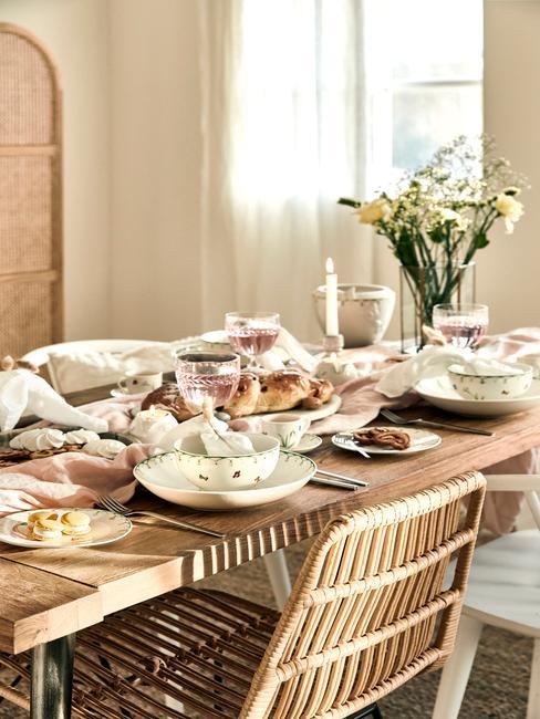 Paasontbijt op een houten tafel met rotan stoelen