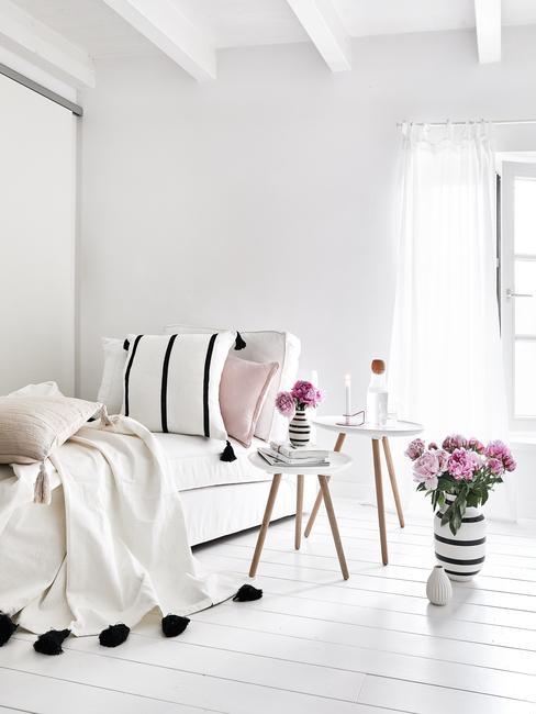 Witte woonkamer met witte belinnen en houten nachtkastje met bloemen baas