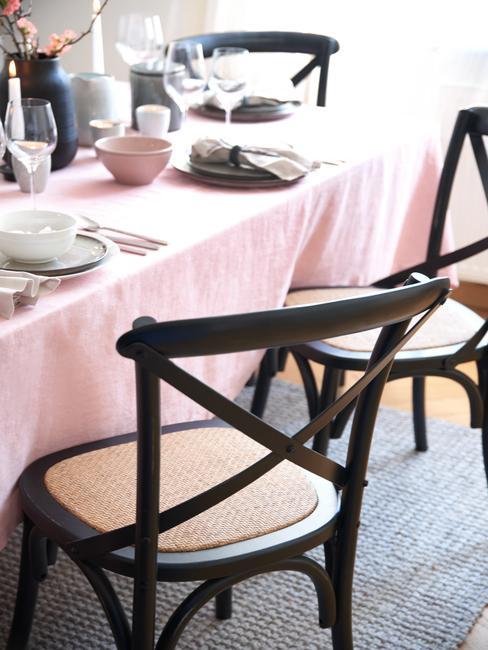 Rotan stoel naast een gedekte tafel met roze bericht geluid
