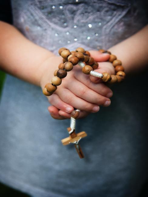 Meisje met een houten rozenkrans in haar hand.