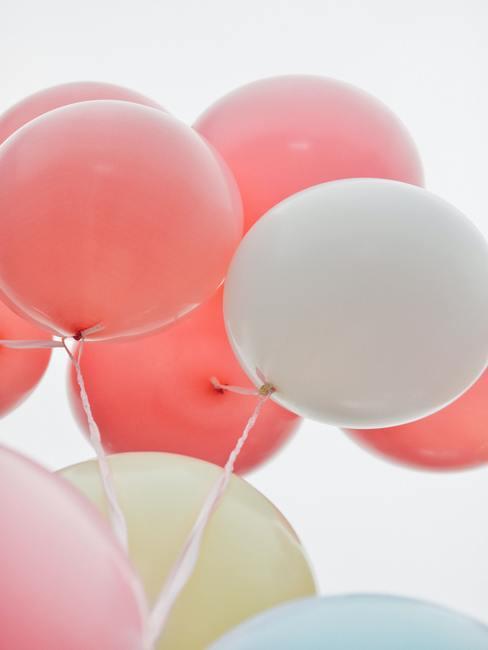 Perzik en witte ballonnen als decoratie op een communiefeest.