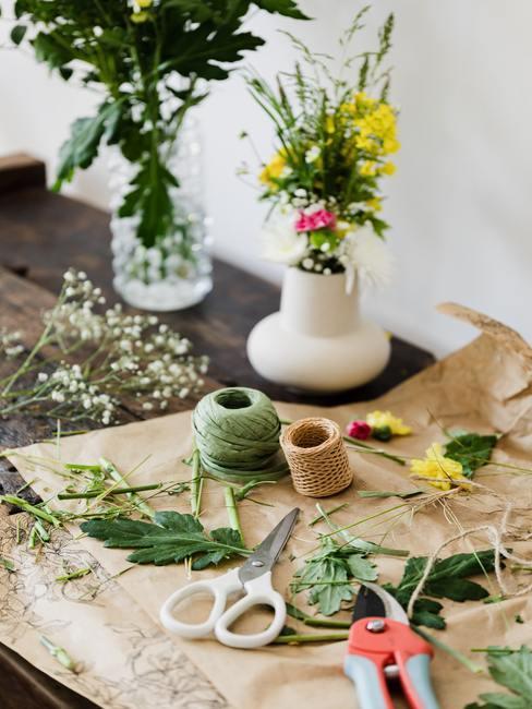vloeipapier op de achtergrond van vers geplukte wilde bloemen en vazen met boeketten.