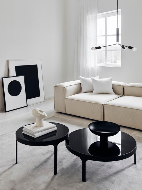 Een moderne woonkamer met witte zitbank met witte kussens en zwarte salontafels met decoraties