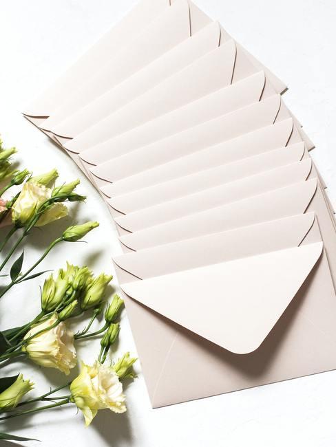 Witte rozen naast creme enveloppen op witte achtergrond